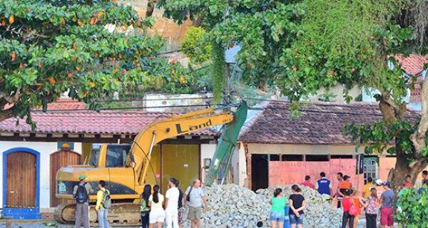Funcionários trabalham na construção de rampa para derrubar mansões