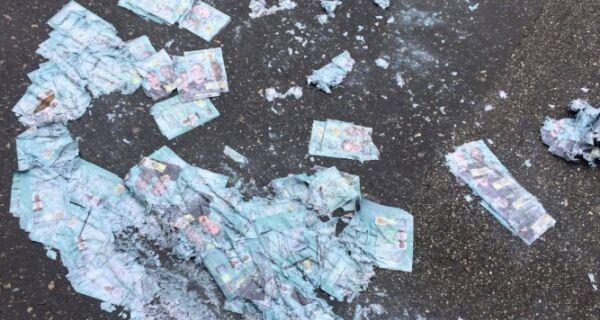 Santinhos deixados no chão são destruídos pela chuva